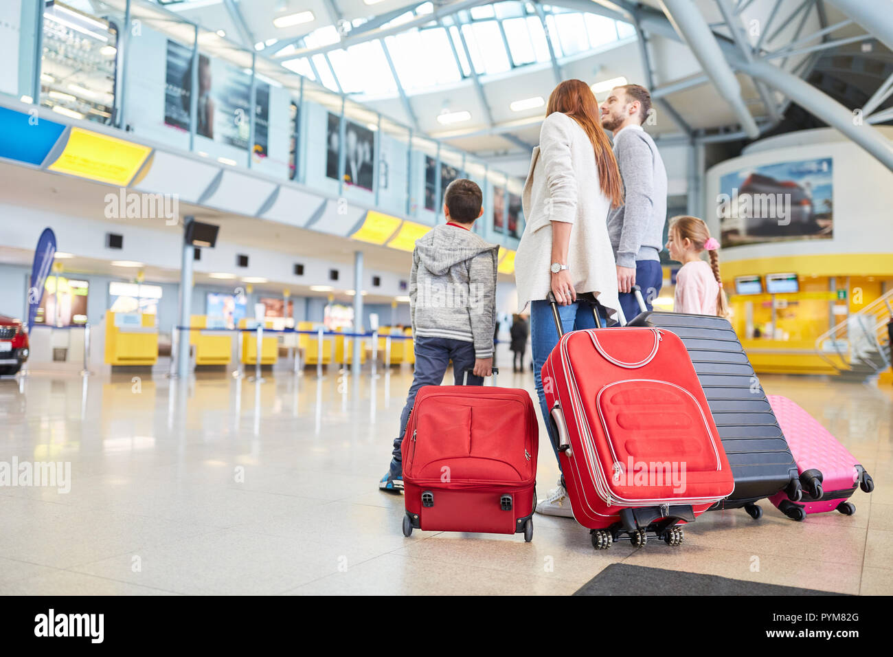Happy family and two children with luggage in the airport terminal are waiting for their departure - Stock Image