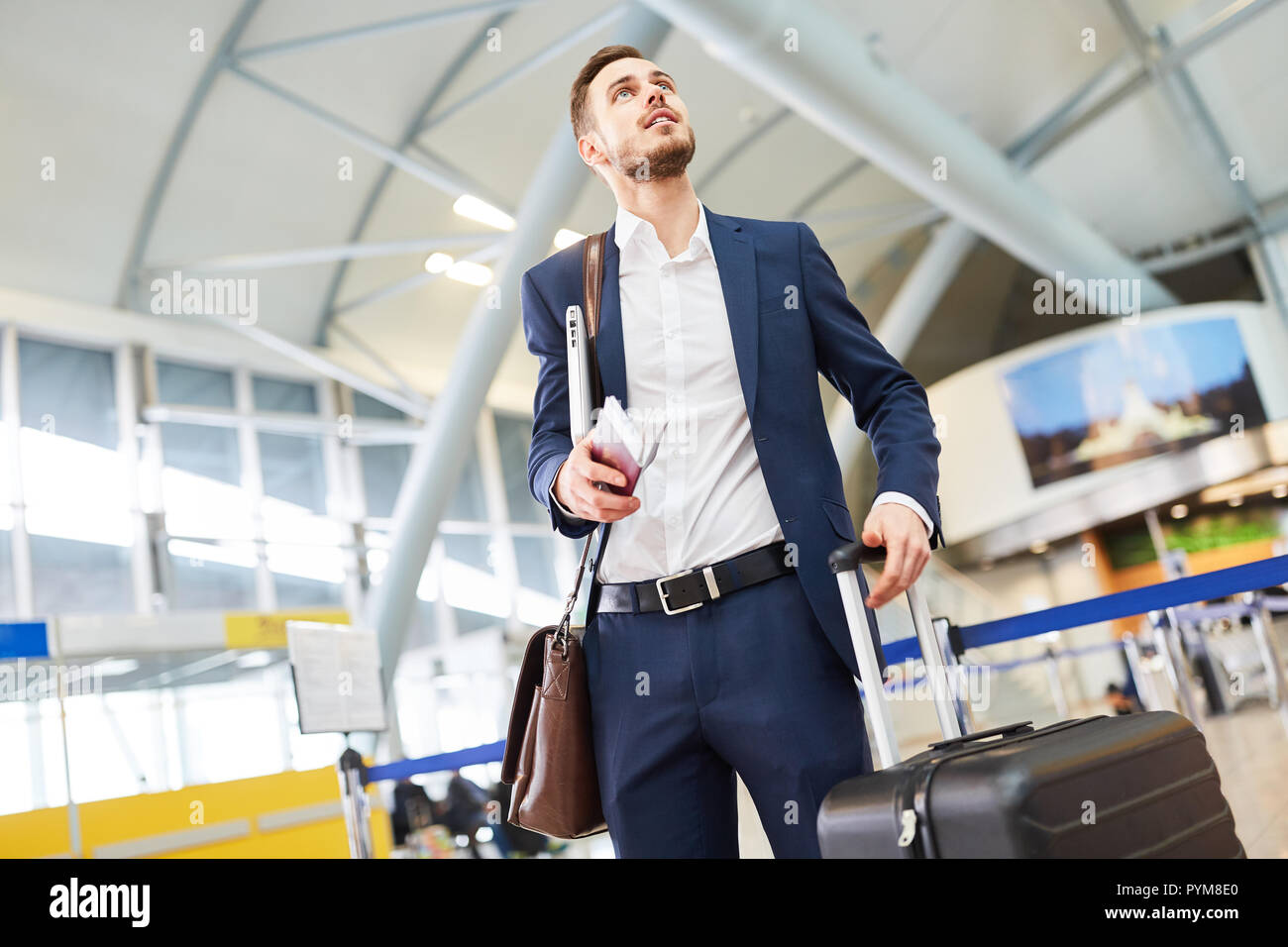 Business man in the airport terminal at the stopover looks for the connecting flight - Stock Image