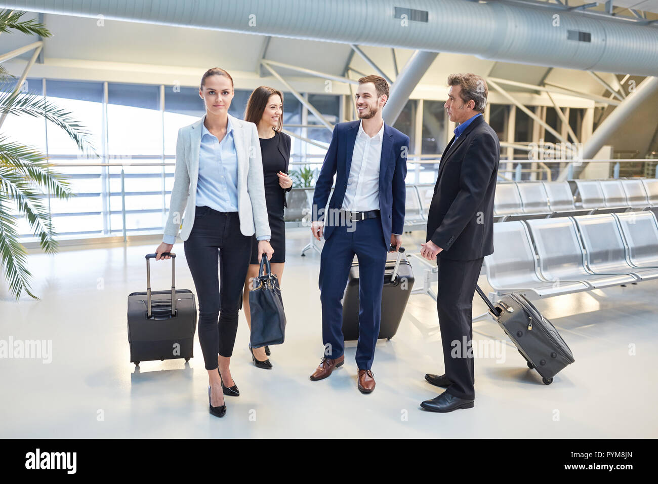 Group Of Business People With Luggage On Business Trip On Arrival In Airport Terminal Stock Photo Alamy