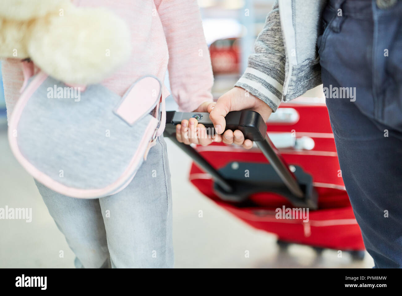 Two children with trolleys in the airport or in the train station take a trip together - Stock Image