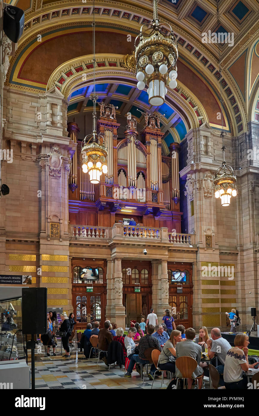 People sitting at Tables and chairs inside the entrance to the Kelvingrove Museum and listening to an Organ Recital. Glasgow, Scotland, UK. - Stock Image
