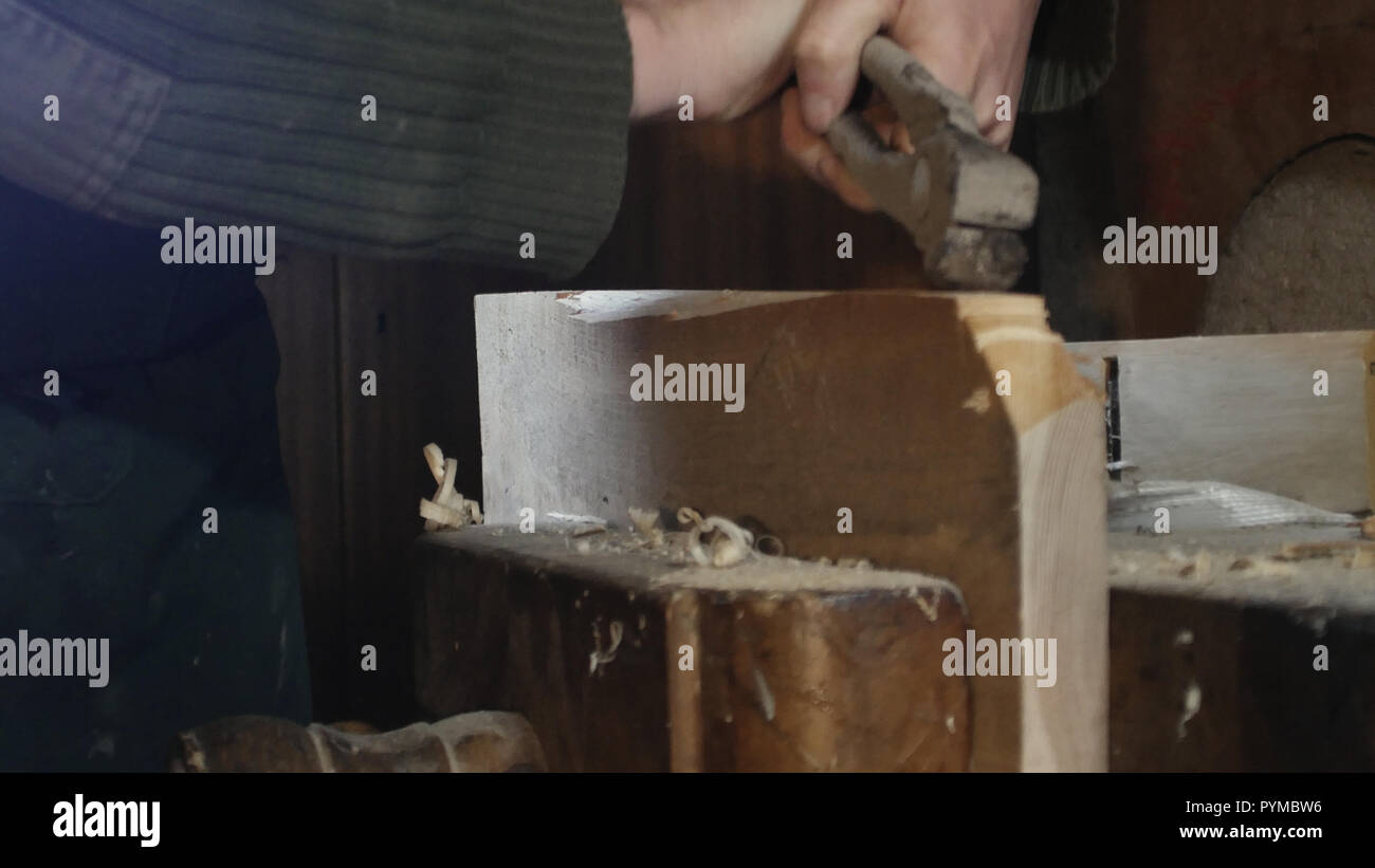 close up, carpenter draws a nail with an antique pincer - Stock Image