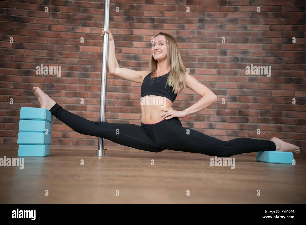 Beautiful young woman does the splits in pole dance studio - Stock Image