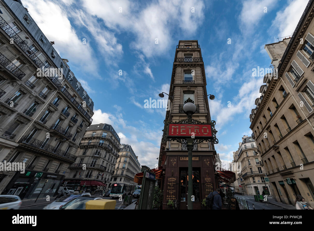 PARIS, 27 October 2018 - View of the typical stone apartment and houses at the Haussmann boulevard with an Metro station entrance and restaurant - Stock Image