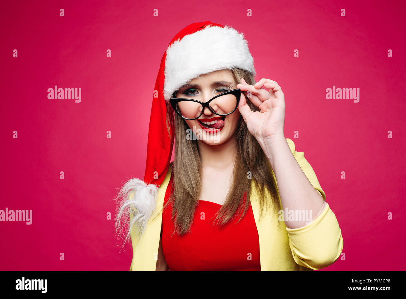 Girl in santa hat and glasses flirting with camera. Stock Photo