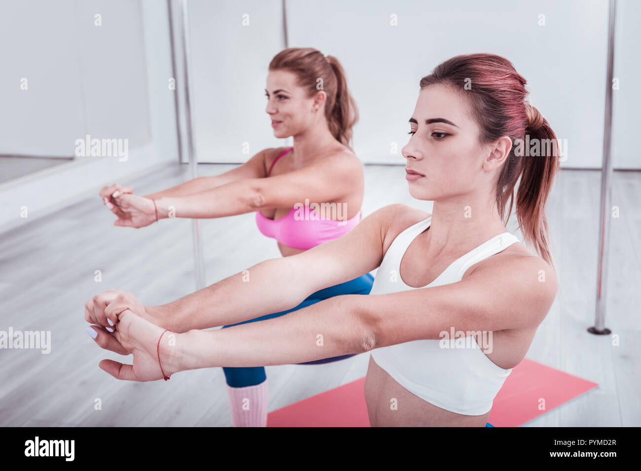 Two women breathing slowly while standing in asana training together - Stock Image