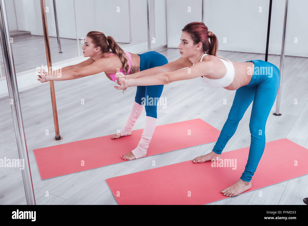 Two pole dancers stretching their legs and backs in pole dance studio - Stock Image