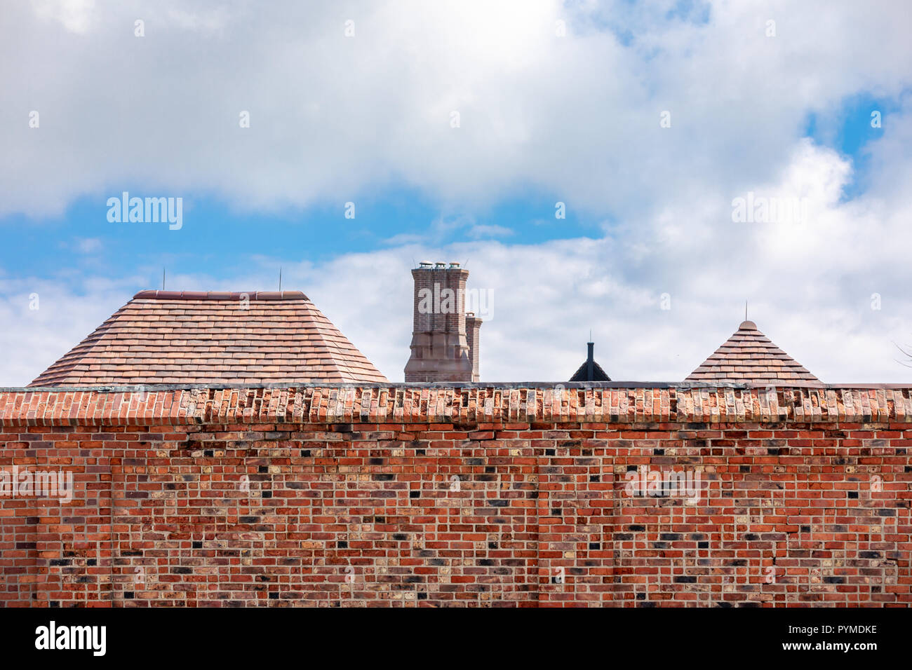 brick wall with the roofs of buildings on the other side - Stock Image