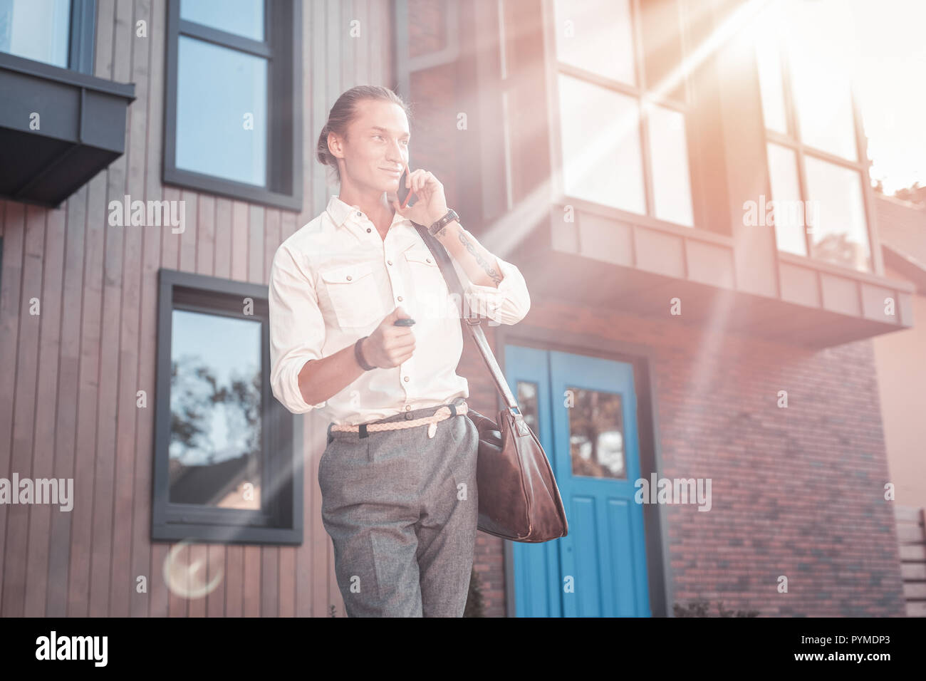Handsome man wearing smart casual clothes speaking by the phone with friend - Stock Image