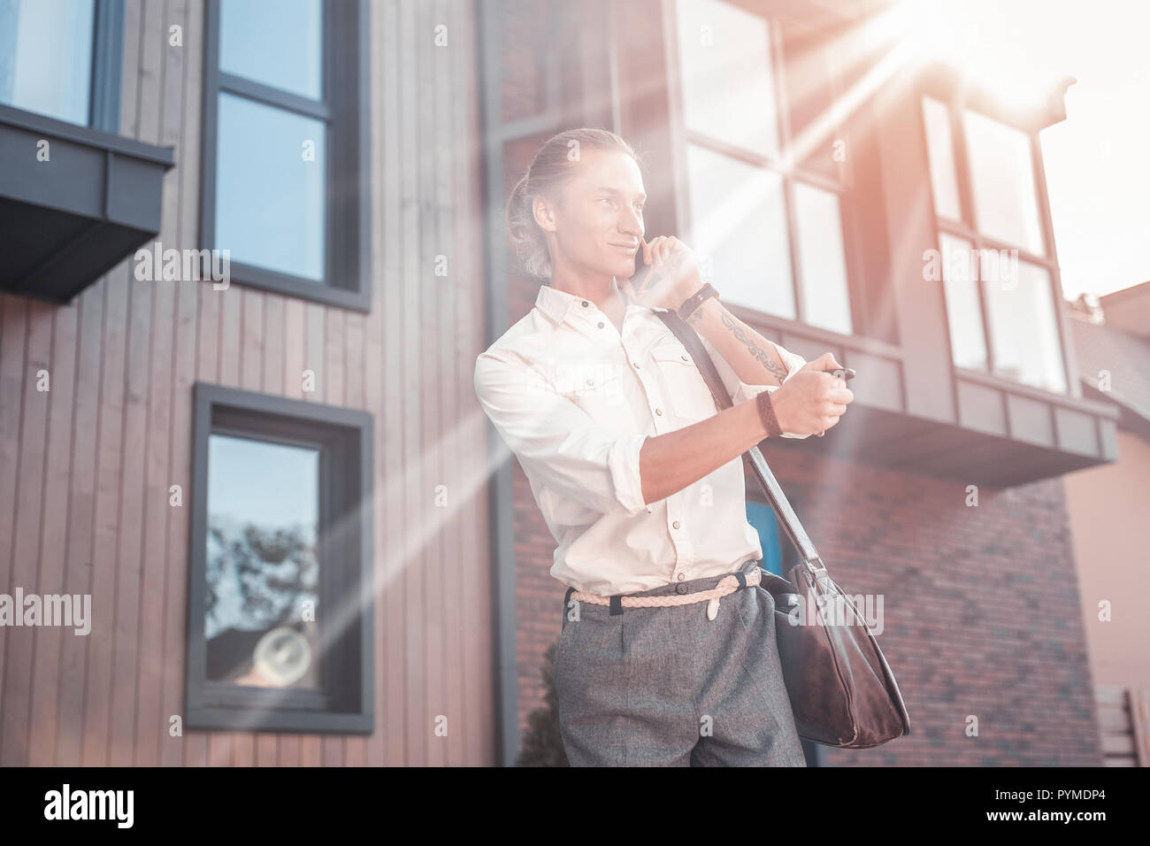 Good-looking man wearing nice hand watch opening car while going to office - Stock Image