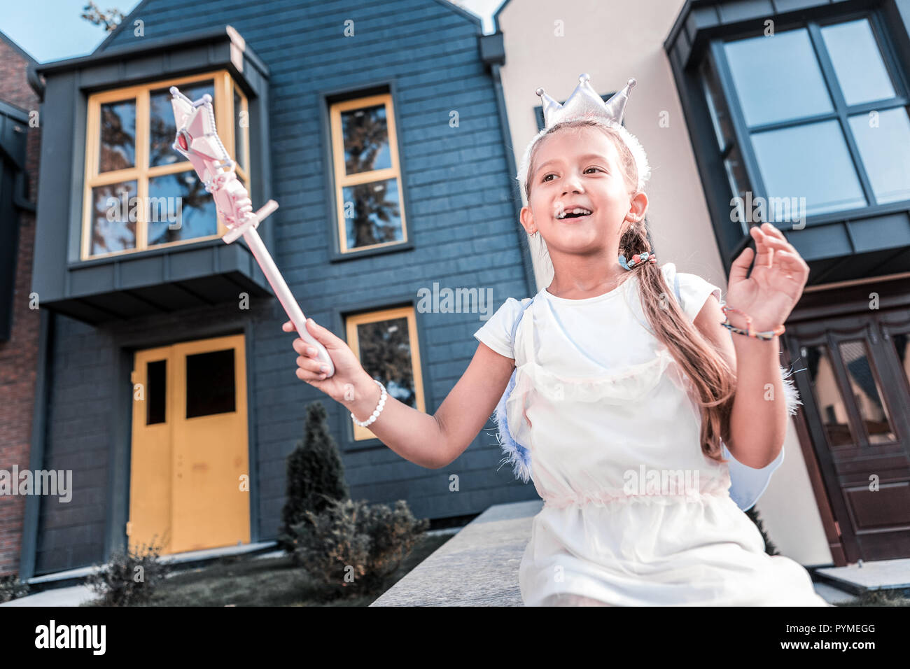 Beaming dark-haired girl with magic wand walking near her house - Stock Image