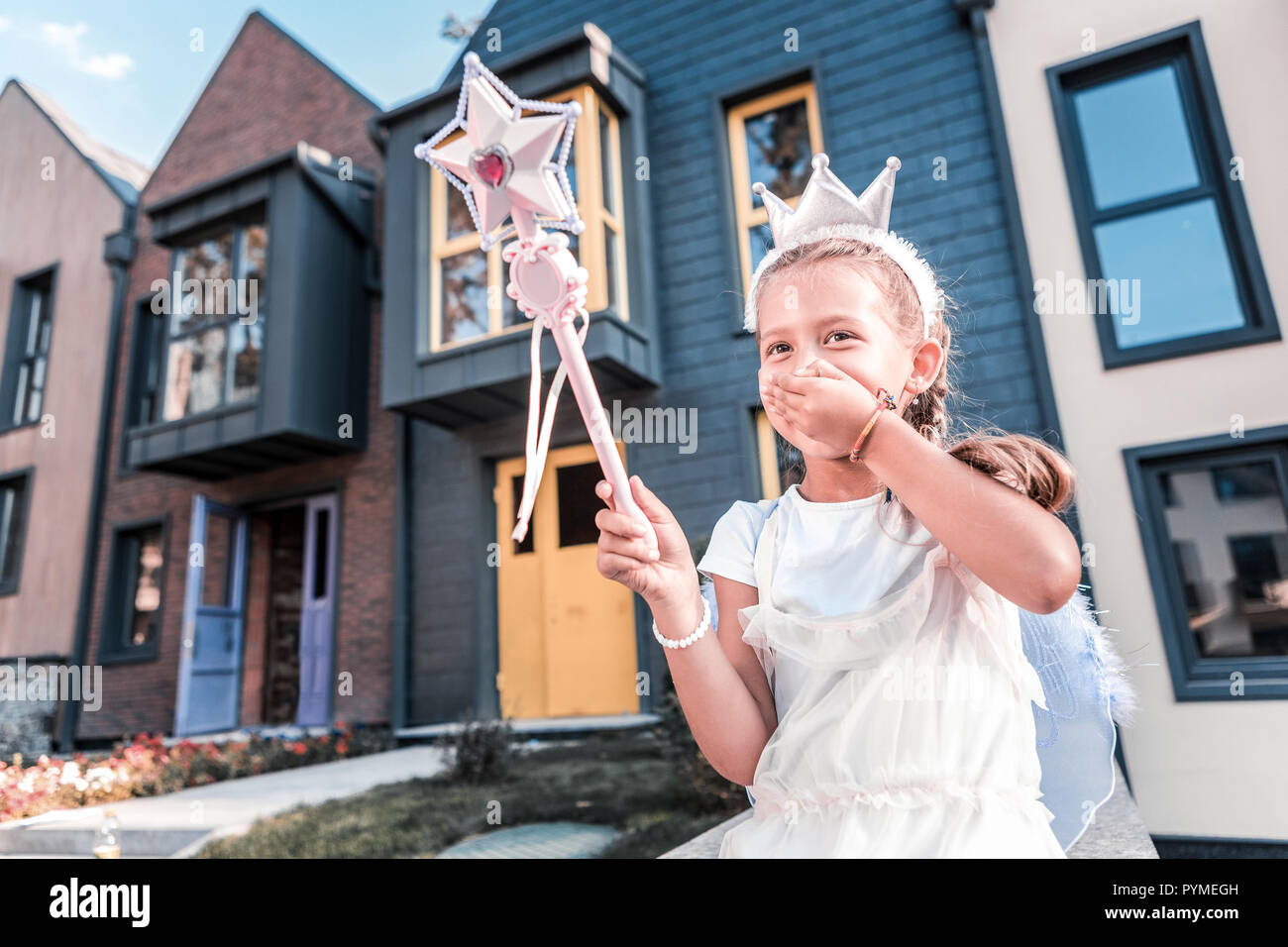 Beautiful girl wearing crown and holding magic wand feeling emotional - Stock Image