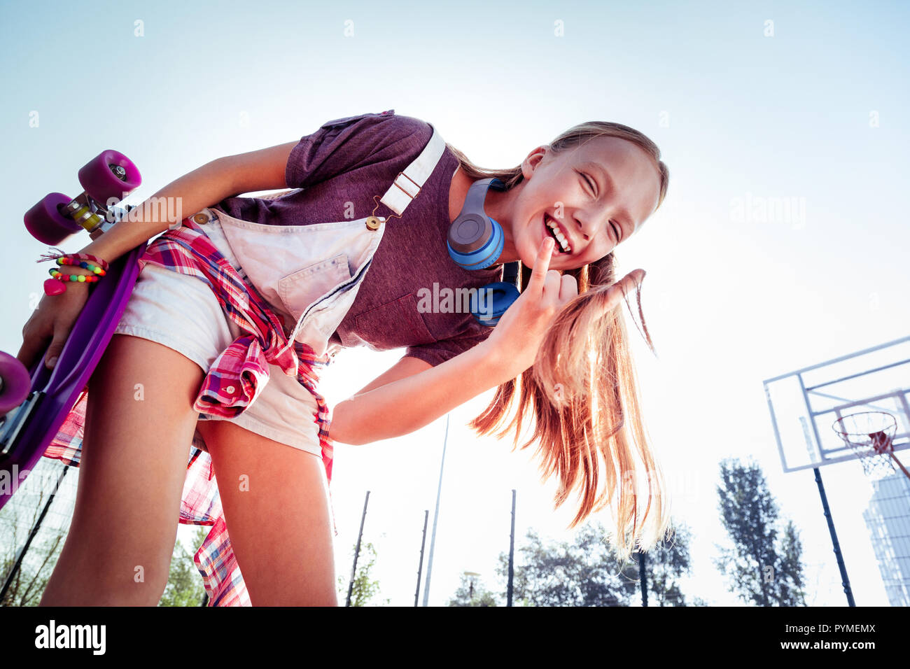 Happy teenager holding her penny-board in right hand Stock Photo
