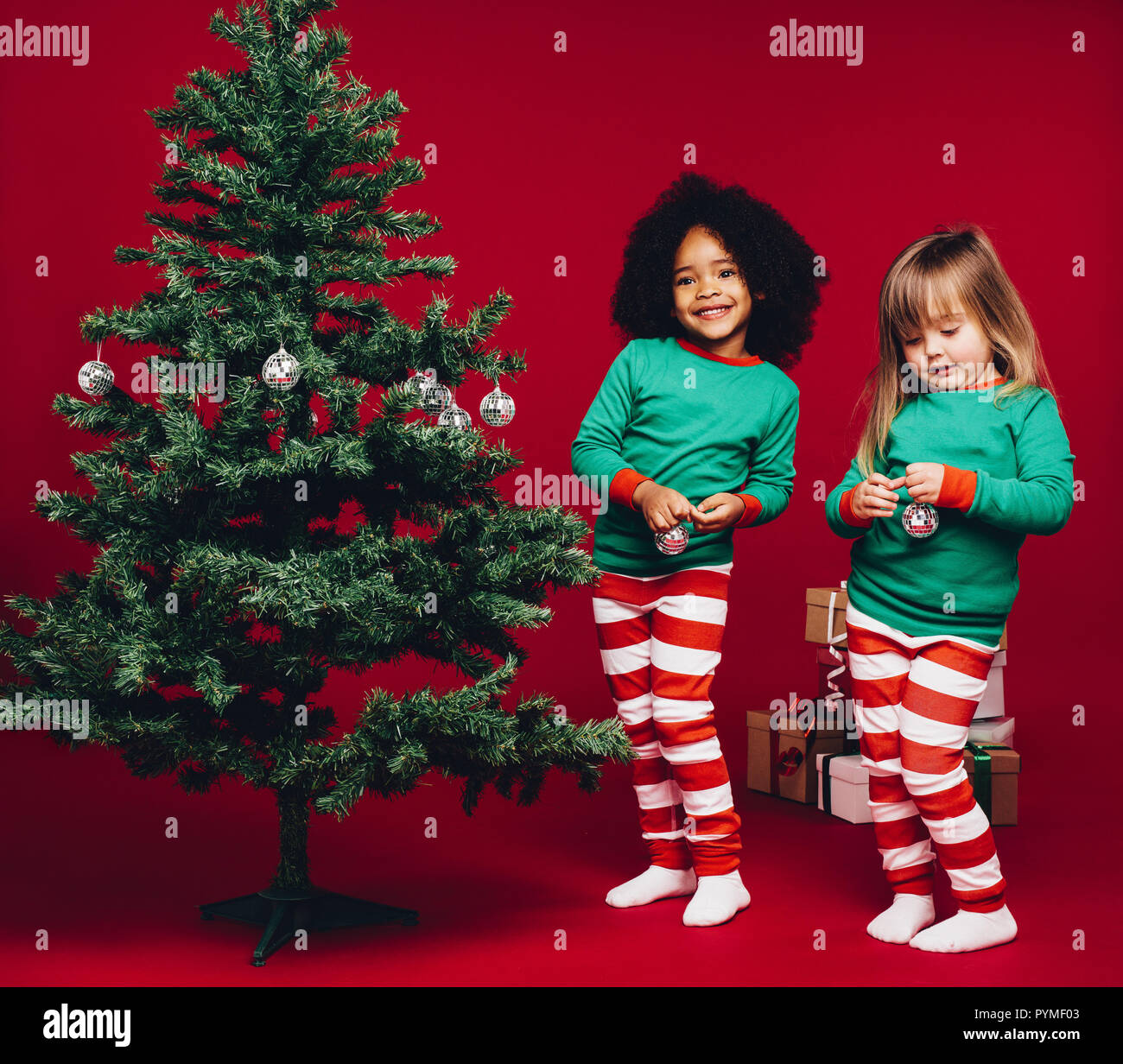 Two Little Girls Standing Beside A Christmas Tree Happy Multi Ethnic Kids Decorating A Christmas Tree Stock Photo Alamy