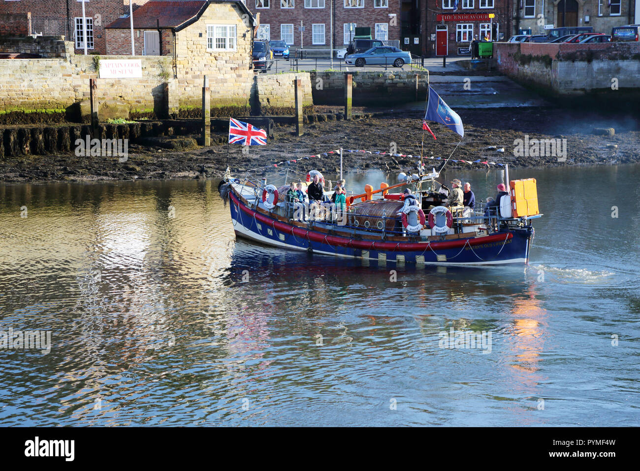 An ex-lifeboat leaves Whitby, North Yorkshire, UK harbour carrying tourists for a trip out to sea. - Stock Image