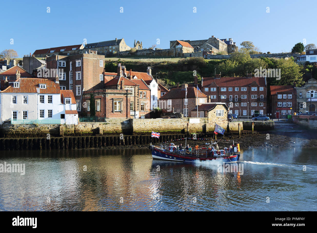 An ex-lifeboat leaves Whitby, North Yorkshire, UK harbour carrying tourists for a trip out to sea. Stock Photo