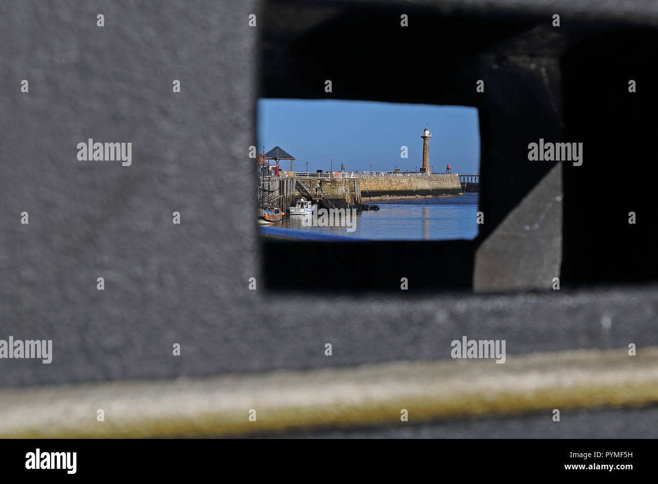 A view of Whitby, North Yorkshire, harbour through a litter bin on a bright autumn, day. - Stock Image