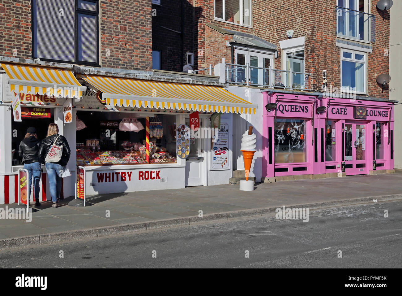 A view of tourist shops alongside the harbour in Whitby, North Yorkshire, UK. - Stock Image