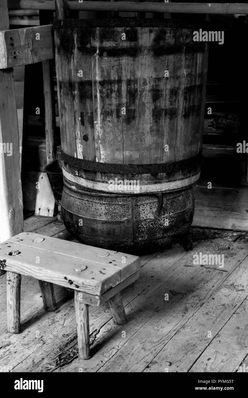 Rustic old oak wooden barrels and milking stool in an old Swedish farm in northern Sweden - Stock Image