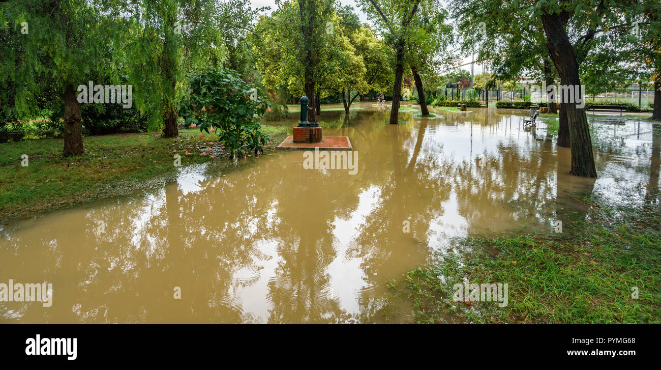 Flooded old Turia river bank after heavy rain with fountain - Stock Image