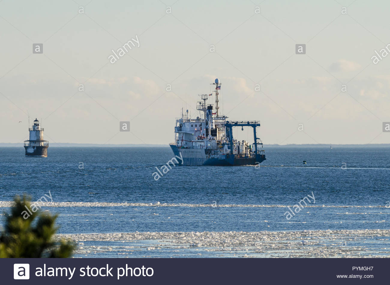 New Bedford, Massachusetts, USA - January 9, 2018: Research vessel Ocean Researcher leaving New Bedford with Butler's Flat lighthouse in background - Stock Image