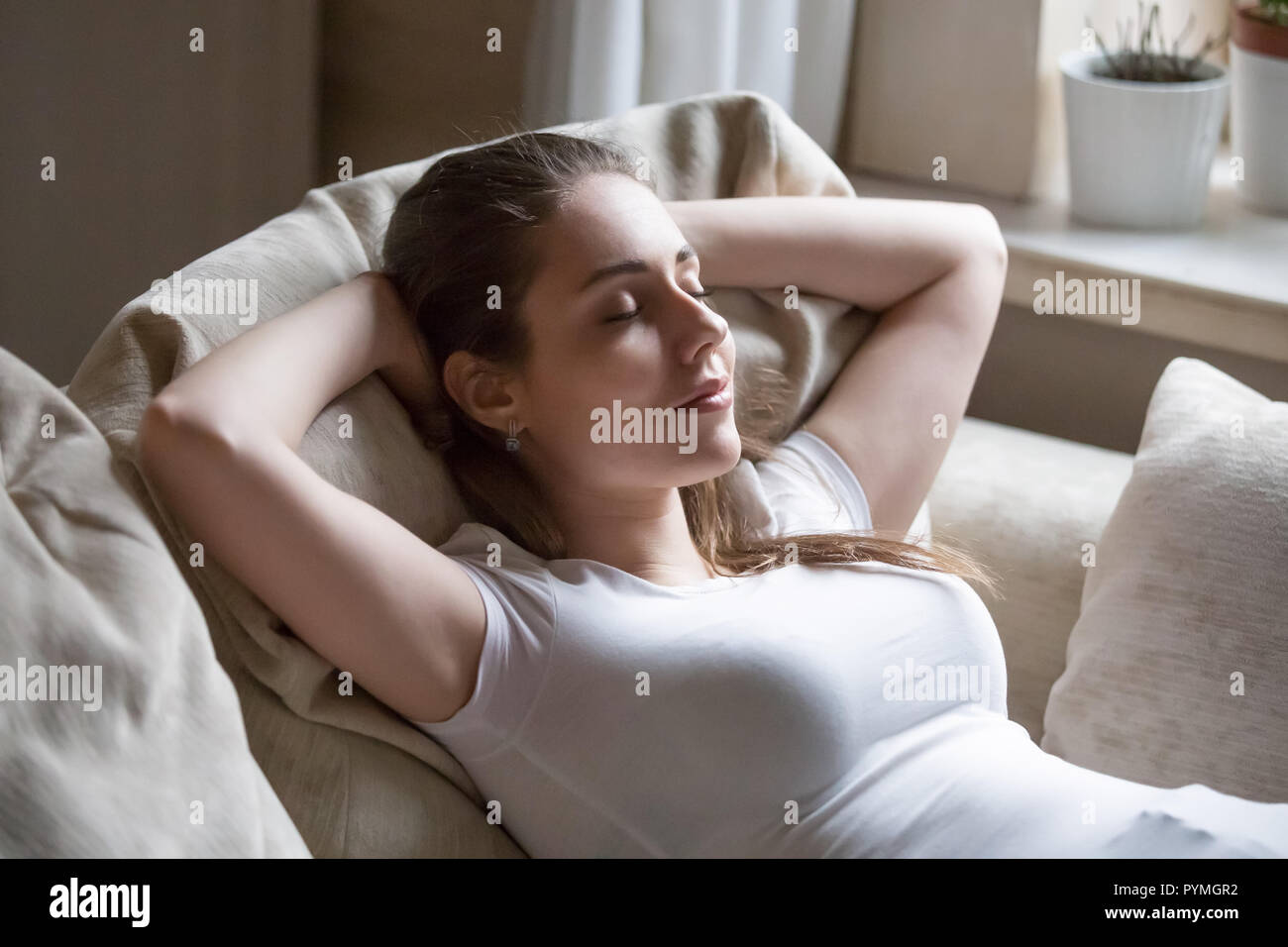 Young positive woman lying on couch relaxing at home - Stock Image