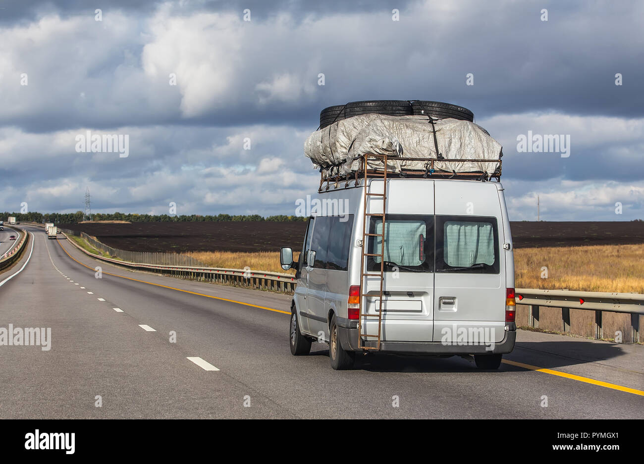 A mini bus with the trunk on top moves along the road. Back view. - Stock Image