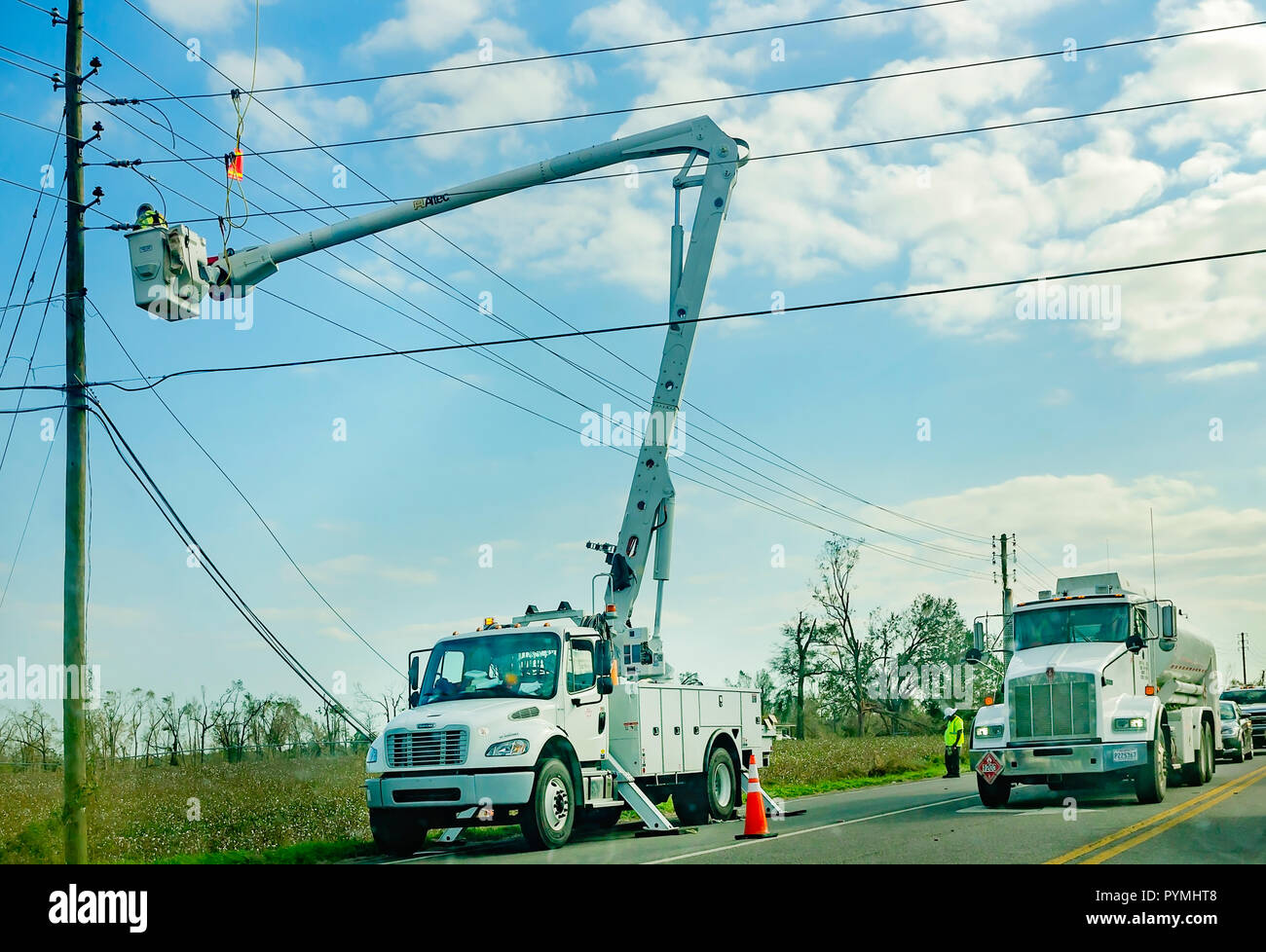 A utility crew lineman works to restore power to a neighborhood, Oct. 18, 2018, in Marianna, Florida. Coastal cities as well as inland cities like Mar - Stock Image