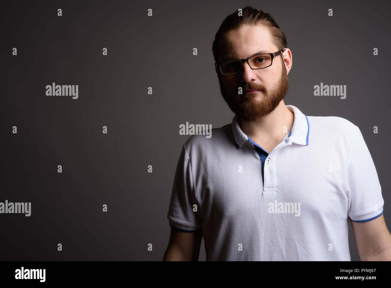 Young bearded man wearing white polo shirt against gray backgrou - Stock Image