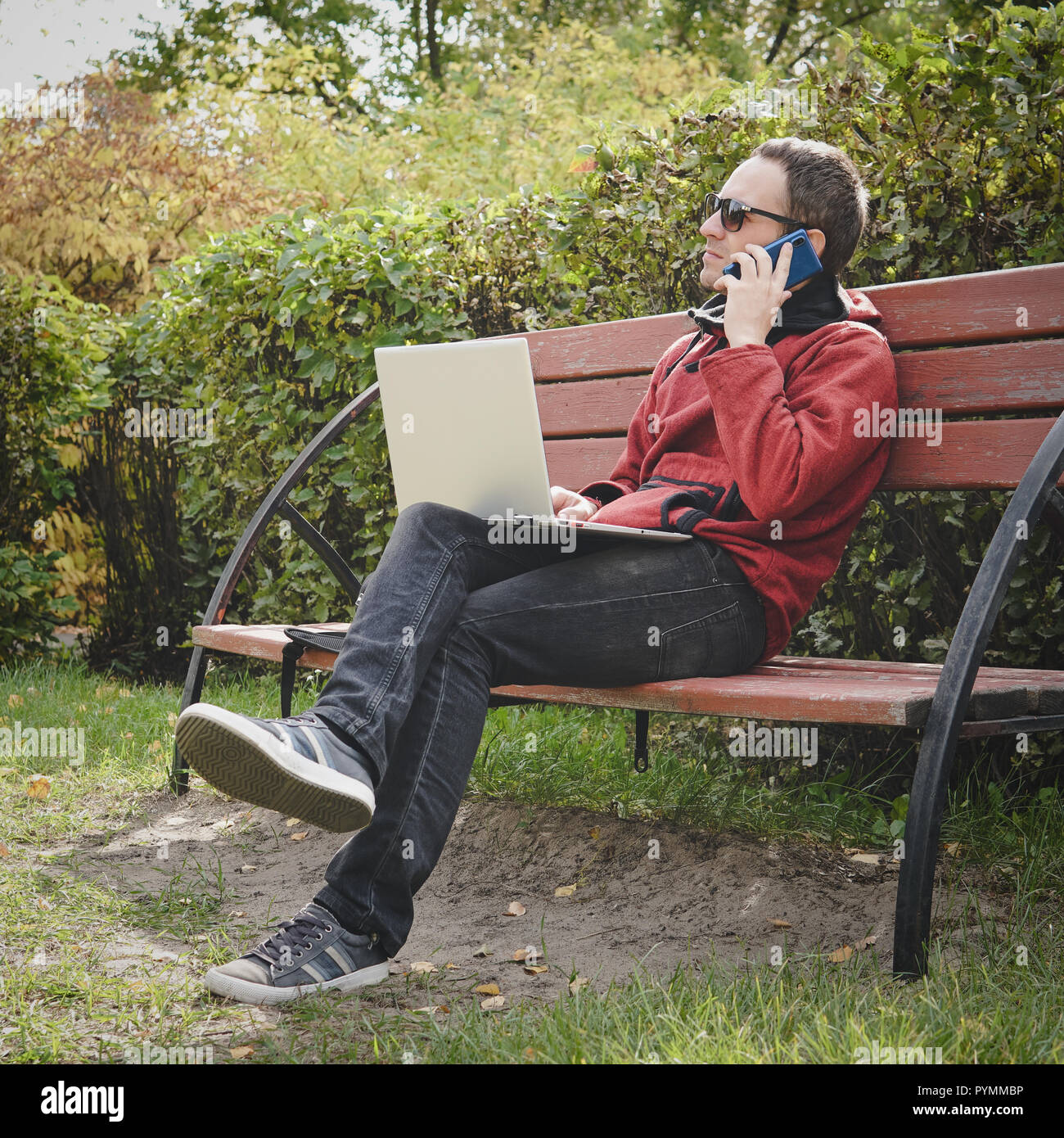man working outdoors always connected with his smartphone and his loyal laptop. young guy, freelancer working outdoors in autumn Park. IT specialist a - Stock Image