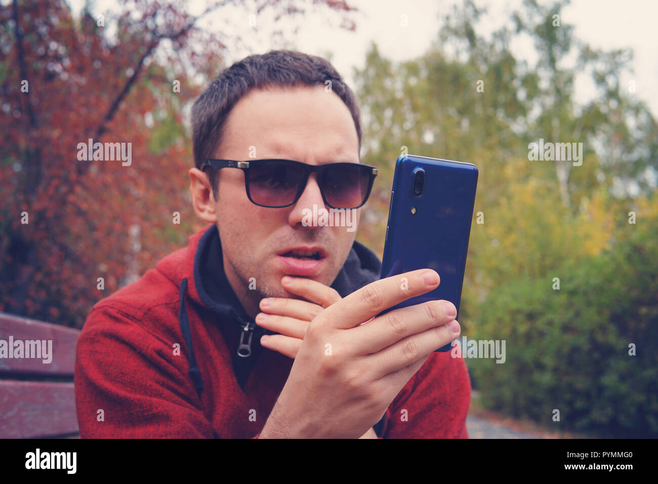 young man in wearing sunglasses holds a modern blue smartphone in his hand and look at the screen with a surprised look. Bewilderment on the face. The - Stock Image