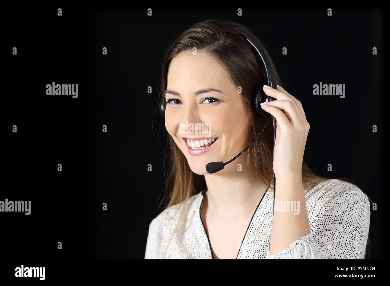 Happy tele marketer looking at camera on black background - Stock Image