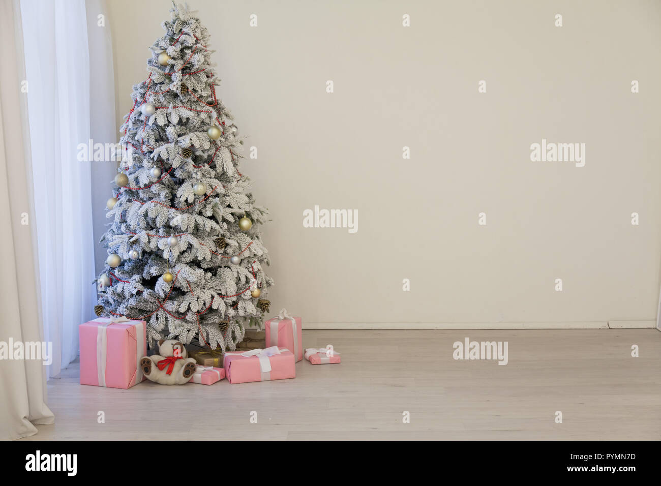 White Christmas tree in Konate with stocking-stuffers - Stock Image
