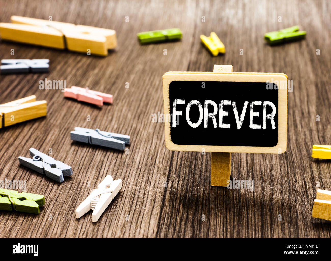 Handwriting text writing Forever. Concept meaning Everlasting Peranalysisent Always for future time endless Eternal Blackboard standing several clothe - Stock Image