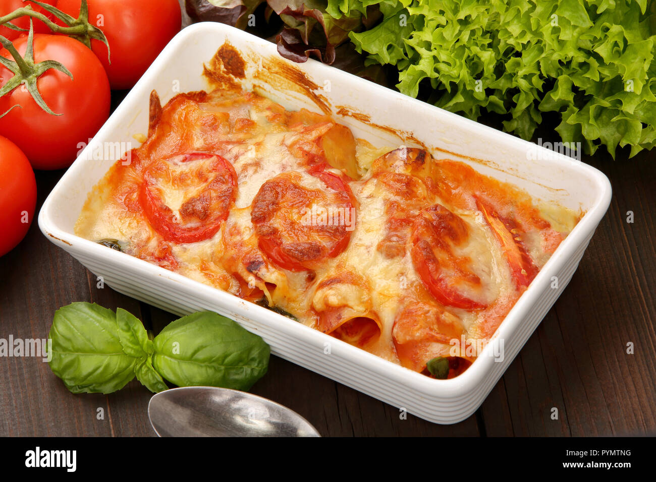 Caneloni stuffed with meat and melted cheese in white bowl over grunge wood background Stock Photo