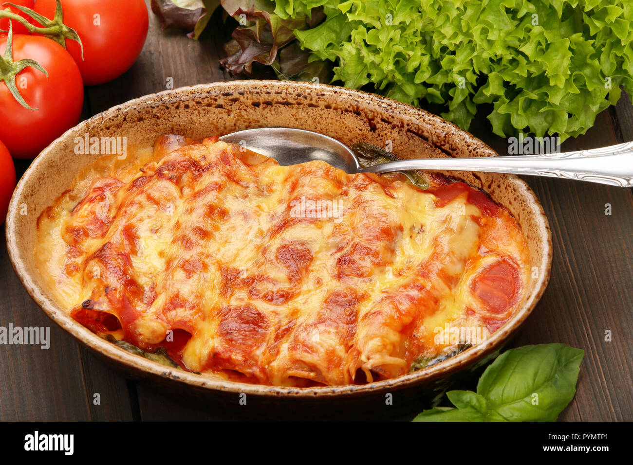 Caneloni stuffed with meat and melted cheese in brown bowl over grunge wood background Stock Photo
