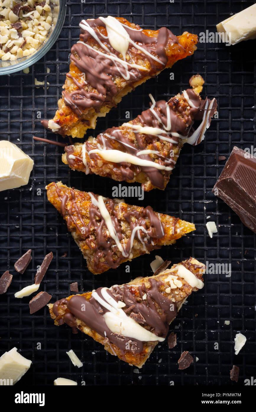 Frische Nussecken serviert auf einem schwarzem Backgitter dekoriert mit Schokoladen Stücken und Spähnen - Stock Image