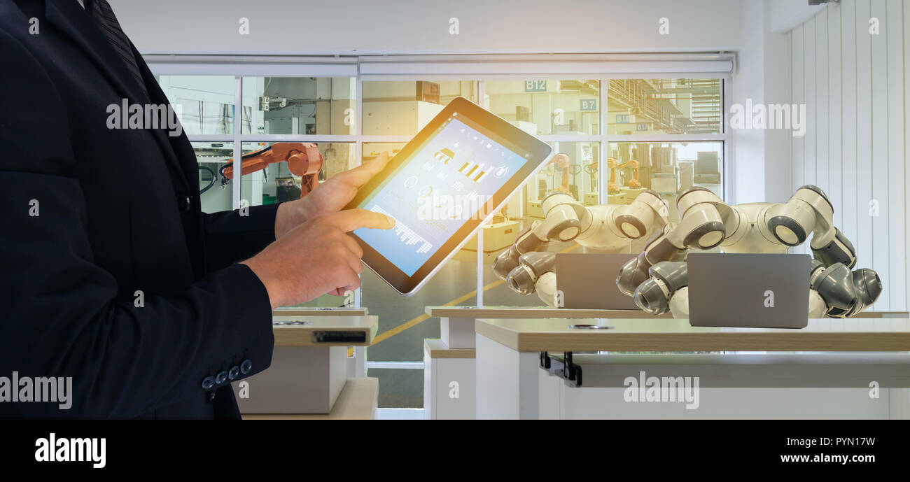 iot smart factory in industry 4.0 robot technology concept, engineer , business man using futuristic tablet to control ,monitor, management robotic to - Stock Image