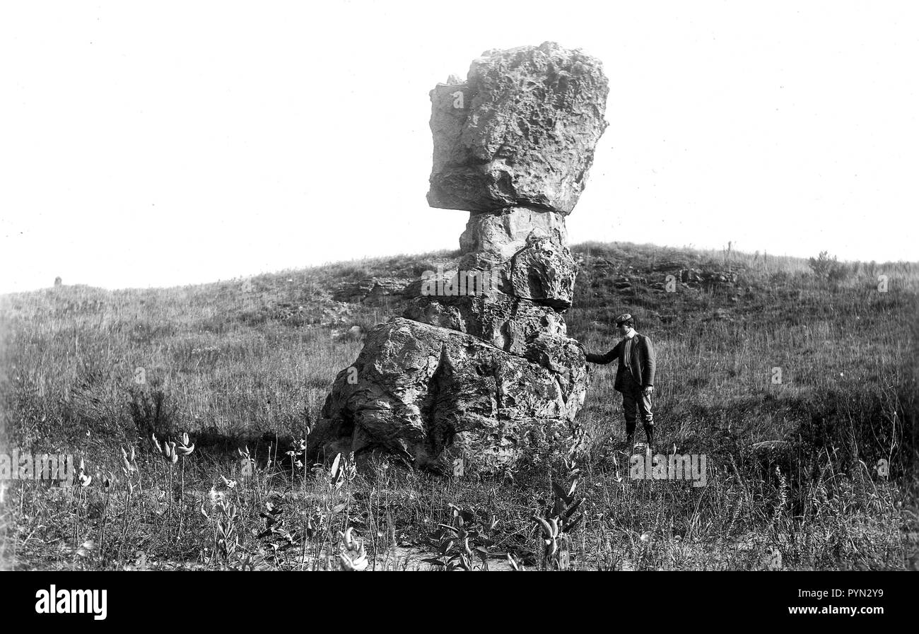 August 28th, 1901 photo of a gentleman with his hand on a leaning tower of St. Peter Sandstone as a result of post-glacial weathering near Footville, Wisconsin. - Stock Image