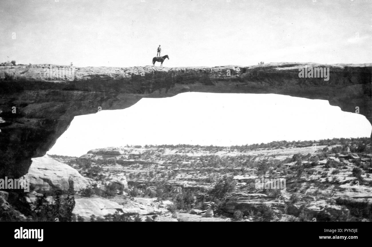 Natural Bridges National Monument in Utah. In this short, we see Dan Perkins (USGS) standing on his horse 'Cap' on top of Owachomo Bridge. - Stock Image