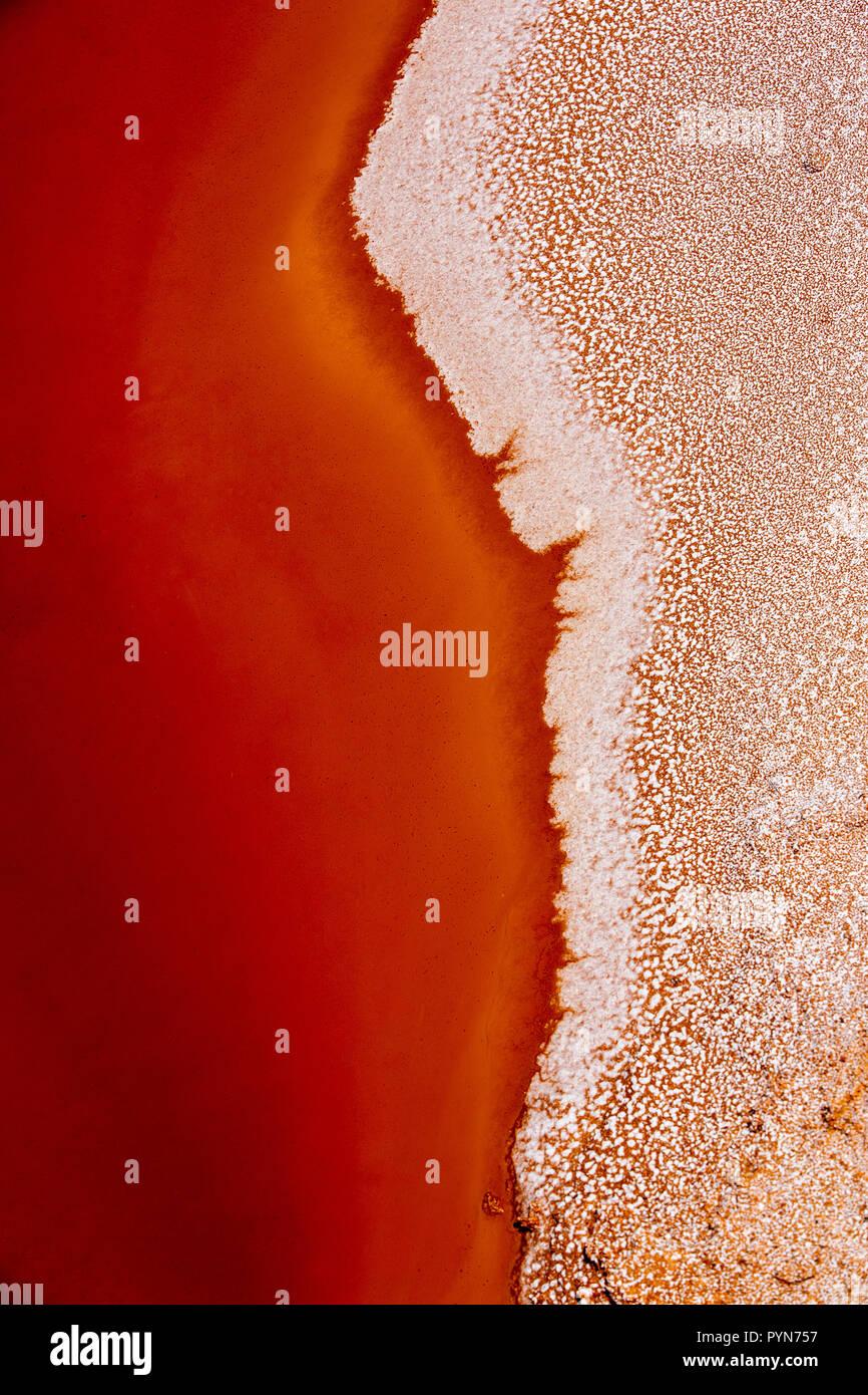 Nahaufnahme eines Salzbeckens in Rot-Oranger Farbe mit Salzkristallen - abstrakte Formen -aufgenommen in einem Salzbecken in Peru, Südamerika - Stock Image