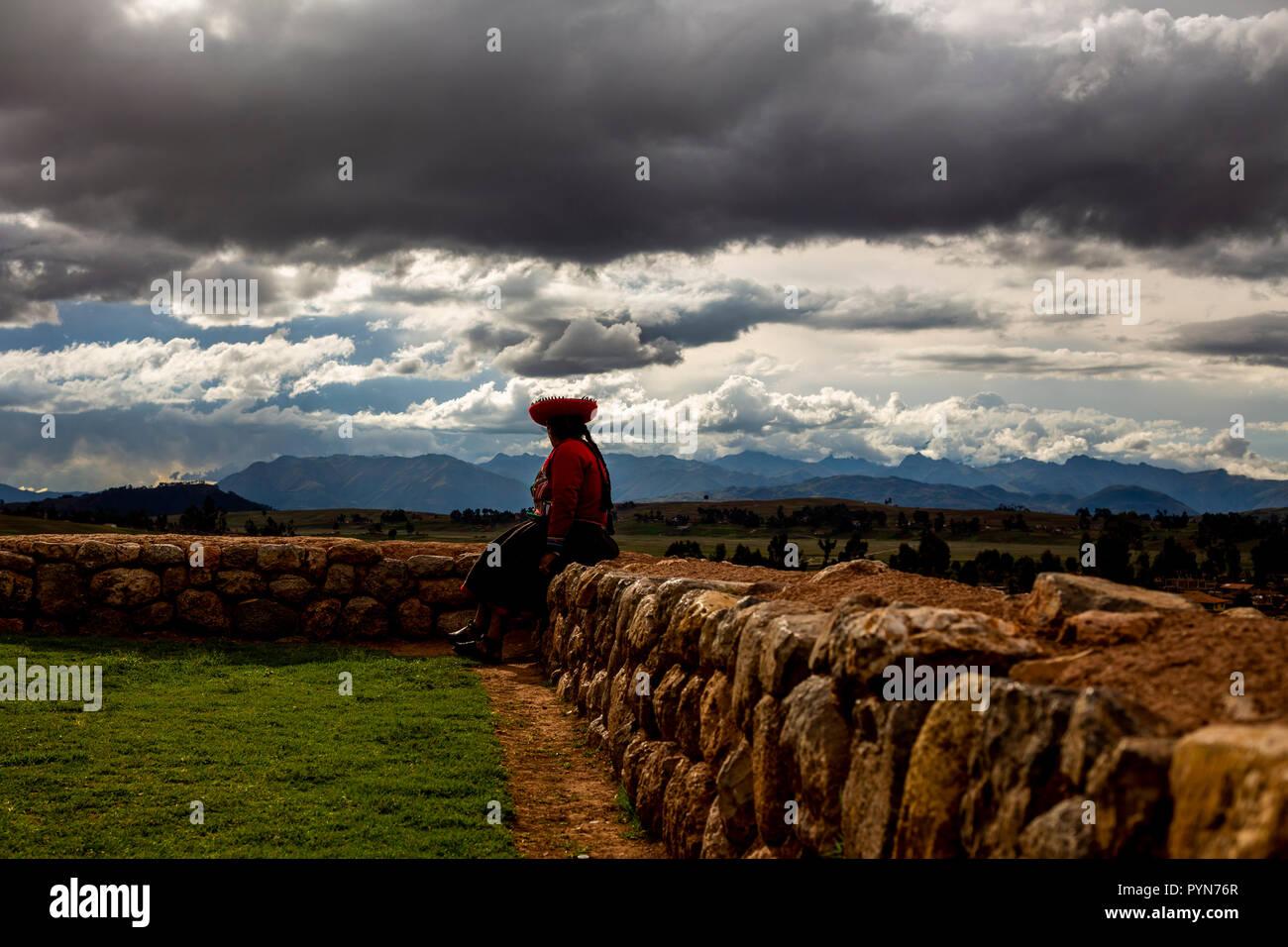 Einwohnerin eines peruanischen Dorfes sitzt auf Steinmauer und schaut auf den Horizont , Peru , Südamerika - Stock Image