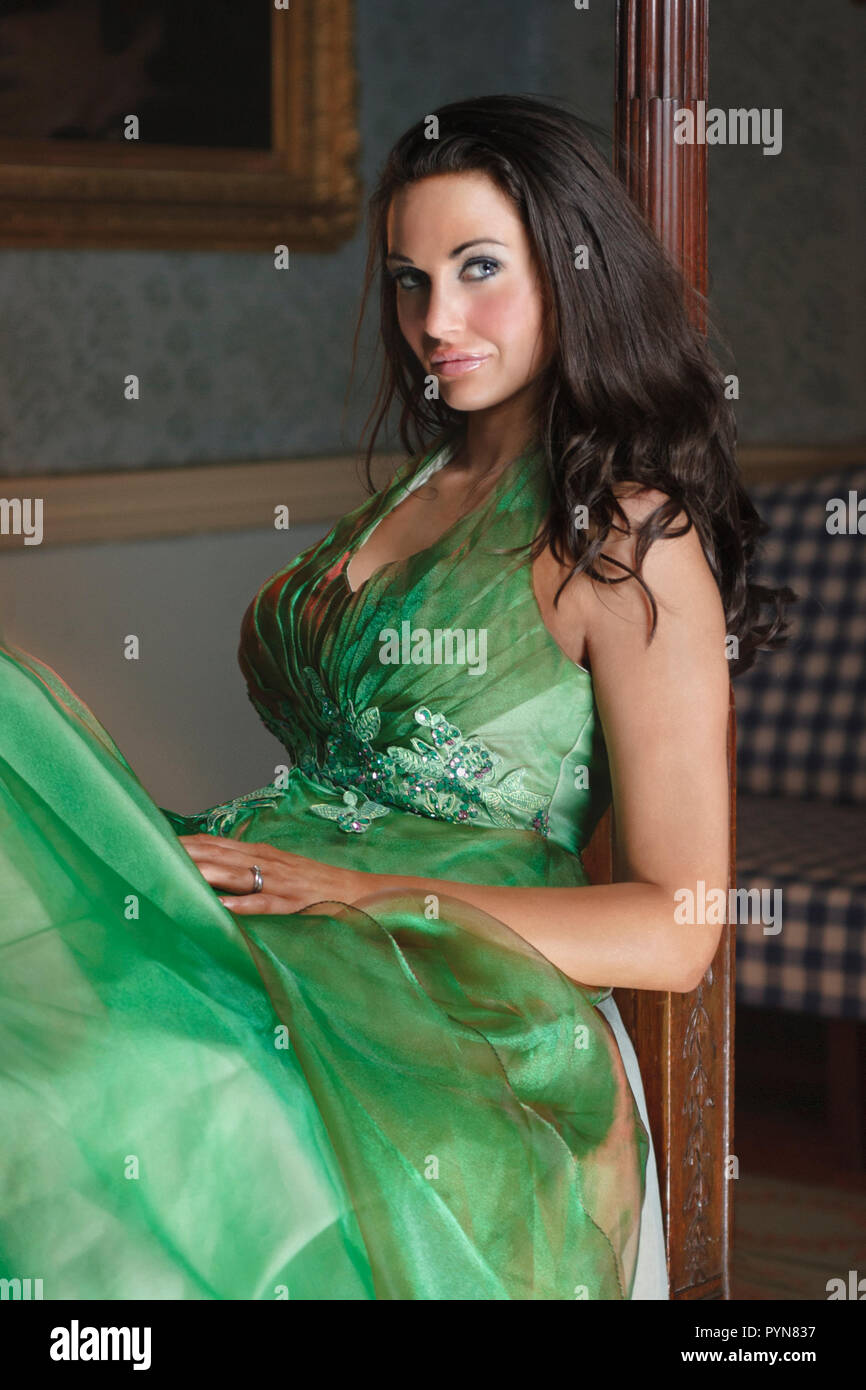 Attractive beautiful brunette young woman in an elegant evening gown sitting up on a four poster bed looking at camera - Stock Image