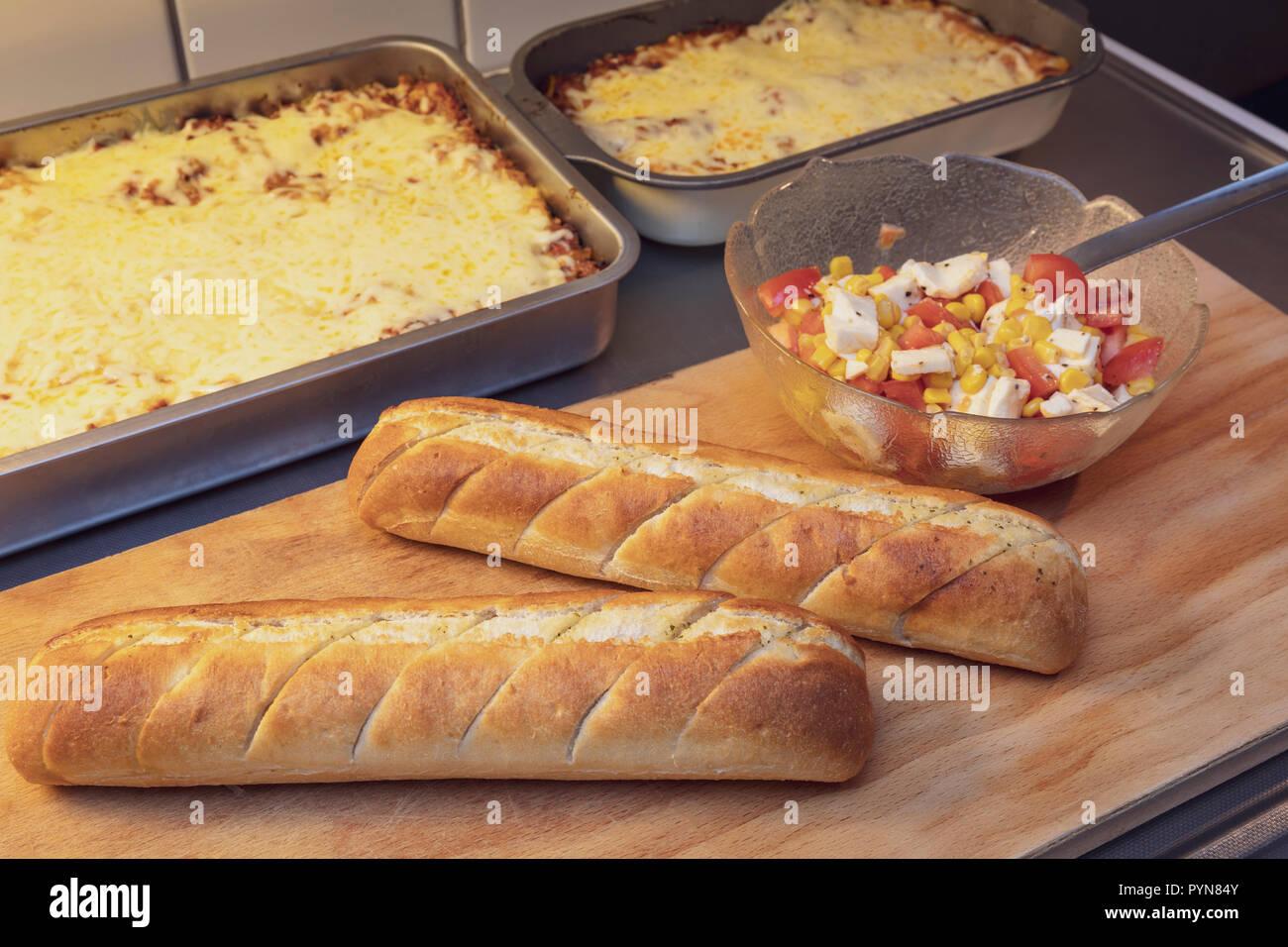 Close up view from above of cooked Lasagna al Forno and vegetarian Lasagna dinner wtih salad and garlic bred - Stock Image