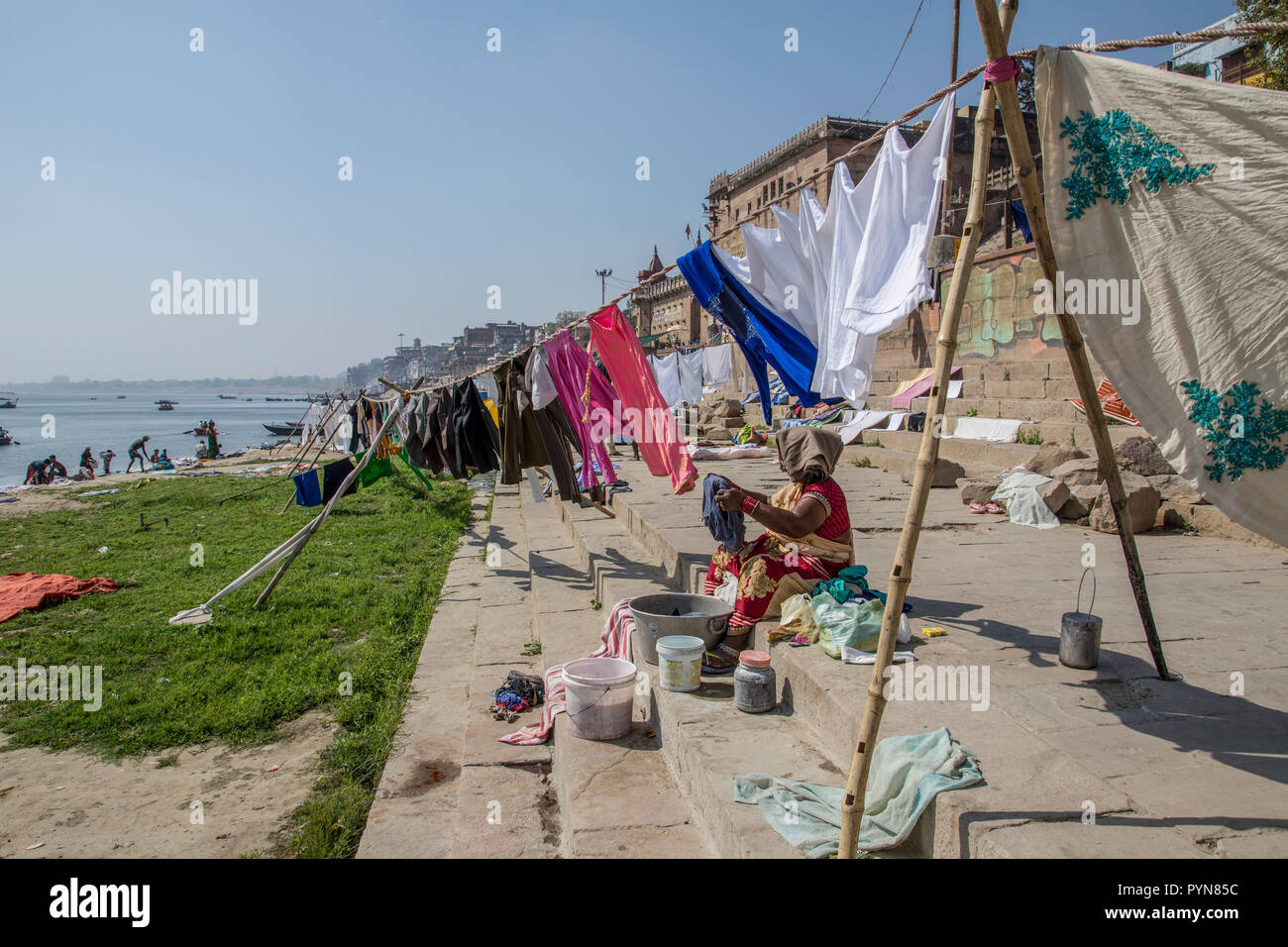 Laundry day on the Ganges river, Varanasi, Uttar Pradesh, India. Clothes and linen are washed in the river and spread to dry on the river's bank - Stock Image
