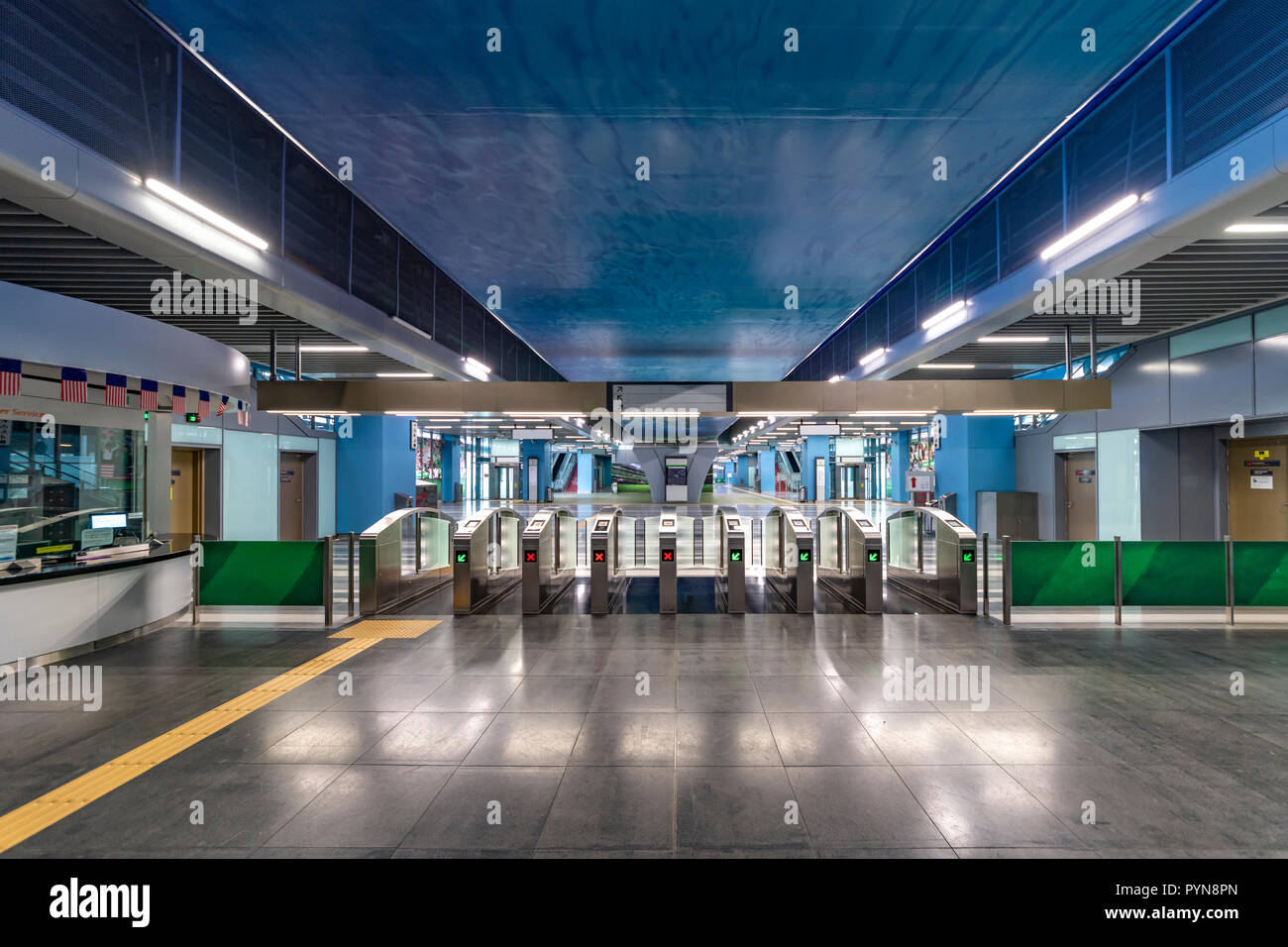 Clean and neat train station with its toll gate reflecting on the marble flooring - Stock Image