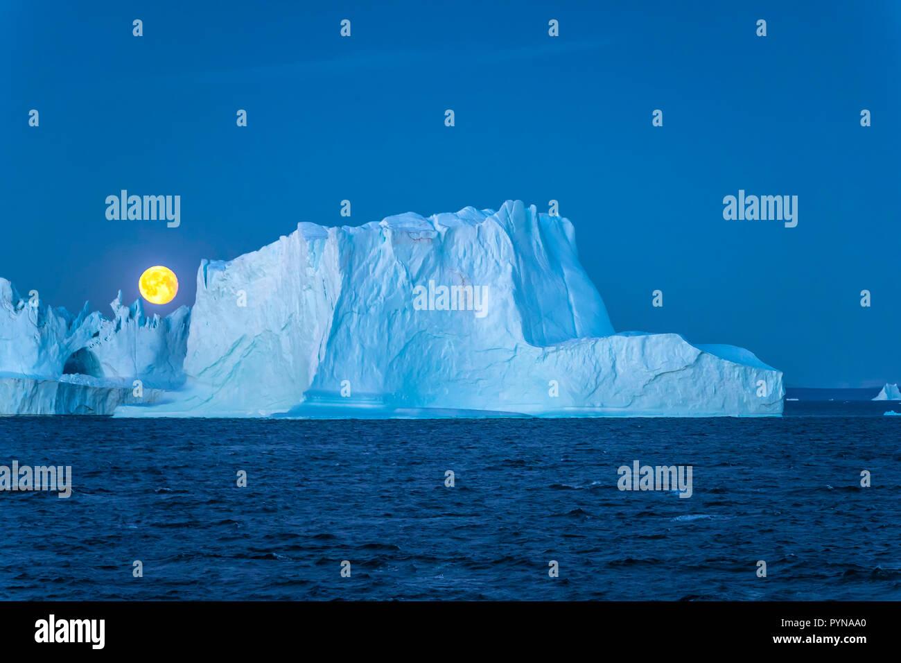 Abendstimmung, Vollmond hinter einem Eisberg, Grönland, Nordpolarmeer, Arktis | Fullmoon behind a iceberg, Greenland, North polar ocean, Arctic - Stock Image