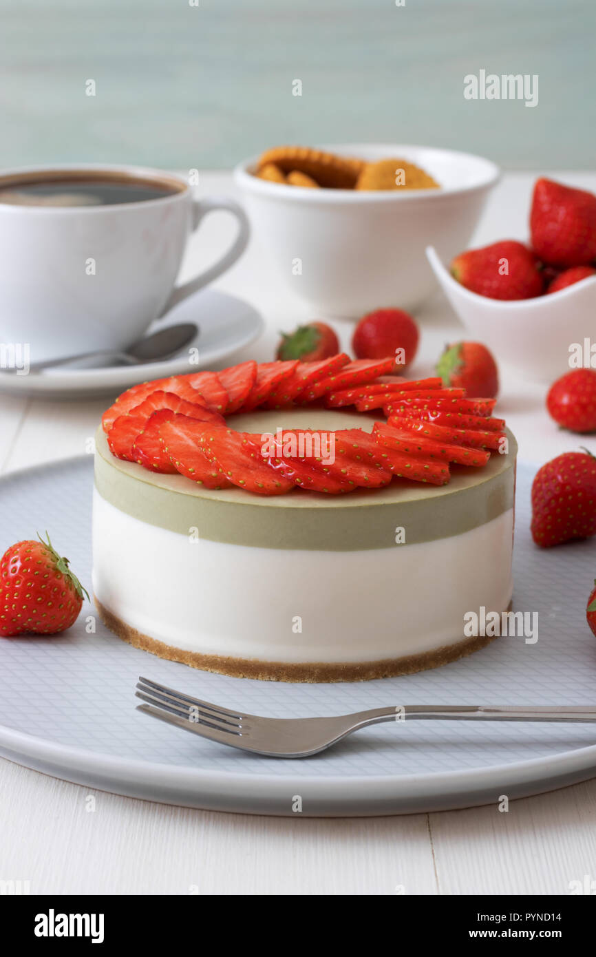Cooking demo. No-bake two-layered mini strawberry matcha cheesecake. Strawberry slices decorate the top of the cake. 3 cups with coffee, cookies and s - Stock Image