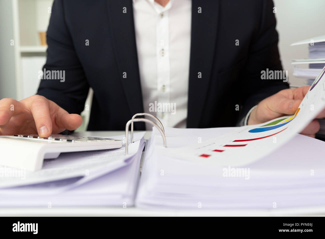 Businessman in a dark blue suit calculating sales results. Finance accounting concept - Stock Image