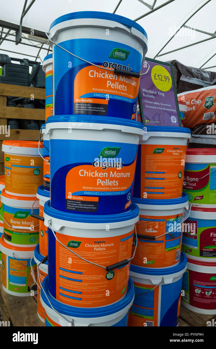 A stack of tubs of organic Chicken Manure Pellets multi purpose compost for sale in a garden centre - Stock Image